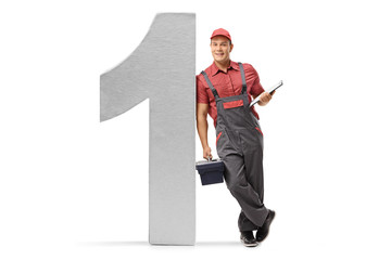 Repairman with a clipboard and a toolbox leaning against a cardboard number one