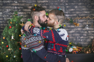 Kissing gay couple with chain of lights at Christmas time at home
