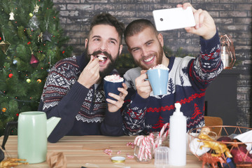 Happy gay couple taking selfie with smartphone at Christmas time at home