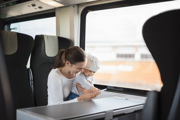 Mother with baby girl traveling by train looking on cell phone