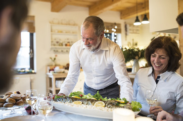 Senior man serving fish for family at Christmas dinner