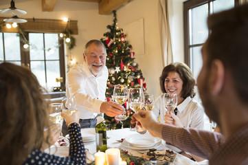 Senior man clinking glasses with family at Christmas dinner