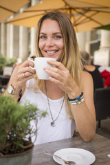 Portrait of smiling young woman in a street cafe