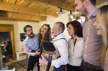Senior man playing accordion for happy family