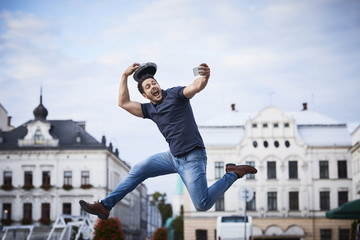 Man jumping and taking selfie holding fedora hat