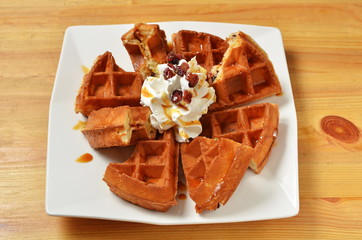 Waffle with whipped cream.caramel and cranberry