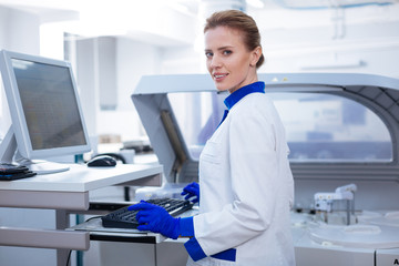 Science in lab. Attractive kind female laboratorian entering data waiting for other results while posing near the medical equipment