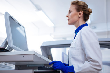 Working hard. Low angle of focused pleasant female scientist staring  at the screen holding hands near the keyboard  standing in the lab