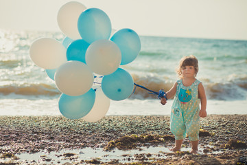 Baby cute girl with blond hair and pink apple cheek enjoying summer time holiday posing on sand beach sea side with blue white balloons wearing casual kids clothes