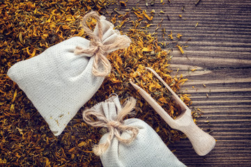 Background of dry marigold medicinal herbs, two sachet bags of aromatic healthy calendula herbs and wooden scoop. Top view.