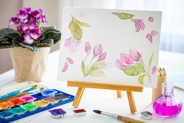 Canvas on easel, watercolor sketch, paints, brushes and violet senpolia flower in pot.