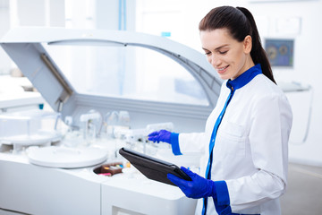 Science is light. Beautiful gentle inspired  female intern smiling adorably and looking at the tablet while stretching her hand to the centrifuge machine