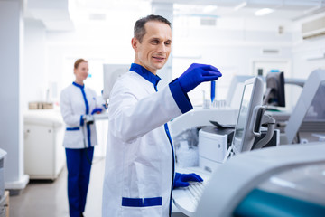 Let me see. Optimistic striking male researcher  smiling and typing while holding test glass in  a hand  near the medical equipment