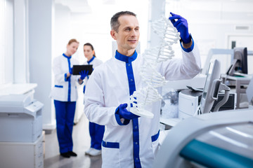 DNA mystery. Wistful happy male scientist carrying DNA and looking for gene  location while posing in the laboratory