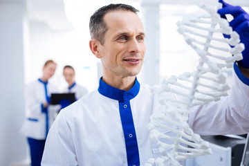 Molecule model. Portrait of thoughtful happy male  scientist who working with DNA model while looking at it and posing against blurred background