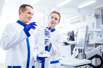 Medical brainstorming.  Attractive pensive male  and female scientists emerging in molecule structure researching  while holding model and standing in the laboratory