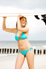 Surfer girl on the beach in bikini.