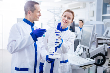 Molecule organization. Happy glad male and female team of scientist examining molecules in DNA and smiling while posing in the lab