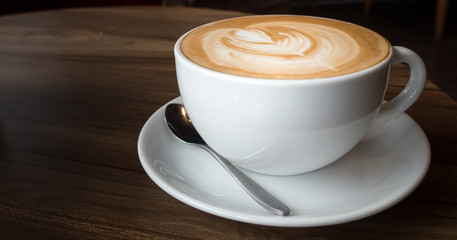 hot coffee in white cup on wood desk