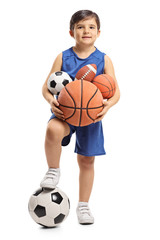 Little boy holding different kinds of sports balls