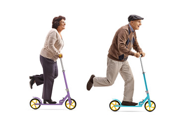 Elderly woman and an elderly man riding scooters