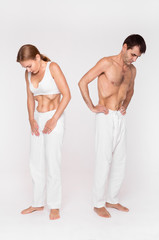 A man and a woman are doing the exercise. Yoga practice. The embroidered stomach. Vacuum of the stomach.