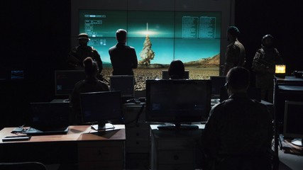 Obraz Authority man giving order to launch nuclear bomb and tracking it on digital screen. - fototapety do salonu