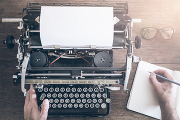 top view of man taking notes besides vintage manual typewriter on rustic wooden table