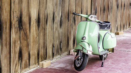 Foto auf Acrylglas Scooter Green scooter against old house. wood wall mossy surface of building as background. Urban street in Thailand, Asia. Moped parked at moldy wood wall. Asian lifestyle and popular transport.
