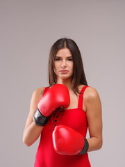 A girl in a red swimsuit and boxing gloves on her hands on a gray background