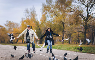 An elderly man and his daughter have fun skating on roller skates. People spreading hands. People and pigeons.