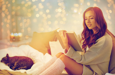 happy young woman reading book in bed at home