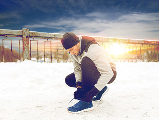 man with earphones tying sports shoes in winter
