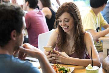 Woman using smartphone in restaurant