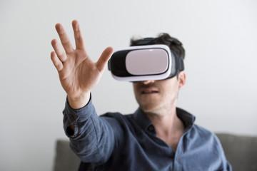 Mid adult man using virtual reality headset