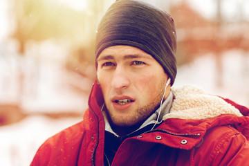 man with earphones listening to music in winter