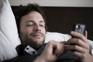 Man reclining in bed using smart phone