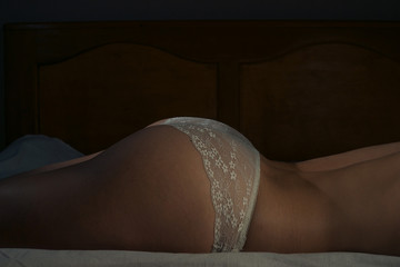 closeup picture of female back and buttocks in white transparent panties on the bed