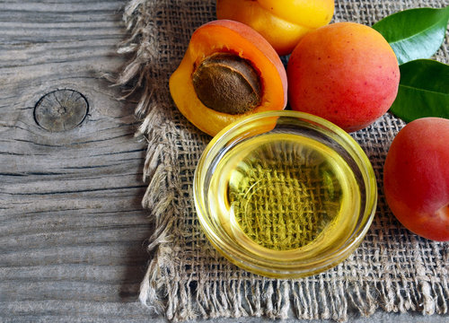 Apricot oil from apricot kernels in a glass bowl and fresh ripe apricots on old wooden background.Essential apricot kernel oil for spa,beauty treatment,aromatherapy and bodycare.Selective focus.