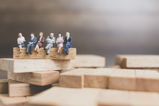 Miniature people : Business People sitting on wood block with wooden background