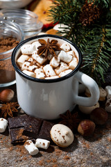 hot chocolate with marshmallows and sweets on wooden background, vertical