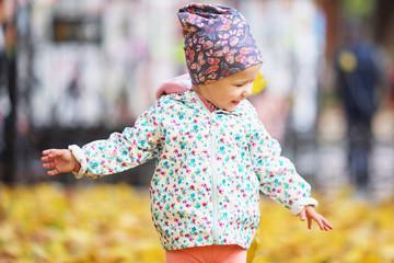Happy urban little girl walking in city autumn park.