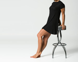Woman in a Cute Black Dress - Barefoot - Sitting on a Stool