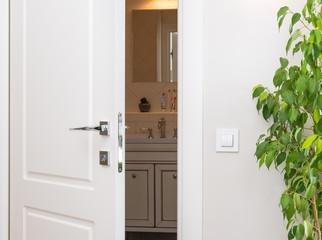 Ajar white door in a dark bathroom. Series switch on a light gray wall. Modern chrome door handle and lock