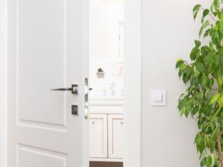 Ajar white door to the bathroom. Series switch on a light gray wall. Modern chrome door handle and lock