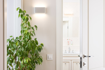 Ajar white door in the bright bathroom. Series switch and modern wall lamp on light gray wall. Chrome door handle and lock