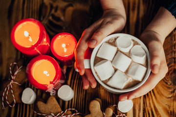 girl woman is holding a cup of cocoa with marshmallow on wooden background. With candles, ginger cookies, on christmas tree background
