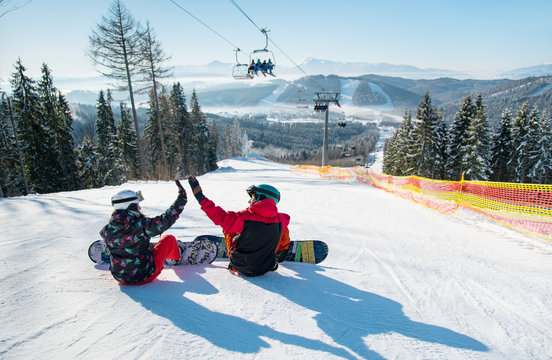 Snowboarders sit on the top of the ski slope under the ski lift let's high five to each other with a beautiful scenery of mountains and forests on a sunny morning