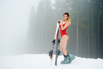 In de dag Wintersporten Young cute woman skier wearing red swimsuit, standing with skis on snowy slope at winter ski resort. Fog, forests on the background. Ski season and winter sports concept