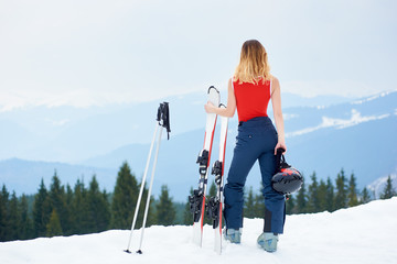 Back view of sporty woman skier wearing ski pants and red swimsuit, standing on the top of the snowy slope with ski equipment at ski resort in the mountains. Ski season and winter sports concept